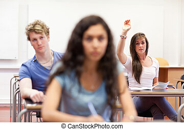 Student raising her hand to give an answer in a classroom