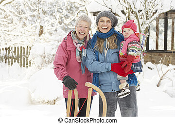 Young Girl With Grandmother And Mother Holding Sledge In...
