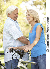 Senior Couple On Cycle Ride In Park