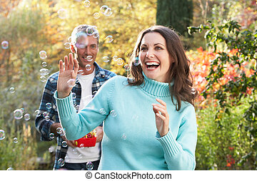 Couple Outdoors In Autumn Landscape With Bubble Machine
