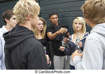 Group Of Threatening Teenagers Hanging Out Together Outside...
