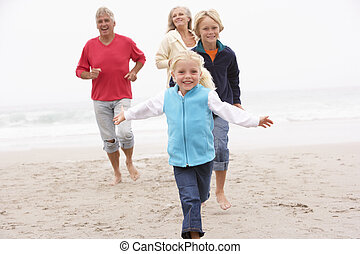 Grandparents And Grandchildren Running On Winter Beach...