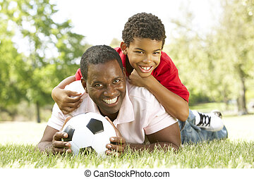Father And Son In Park With Football