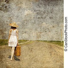 Lonely girl with suitcase at country road.. Photo in old...
