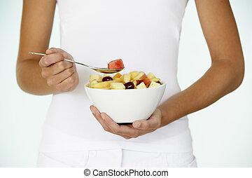 Young Woman Eating Fresh Fruit Salad