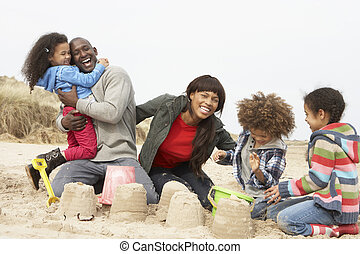 Young Family Building Sandcastle On Beach Holiday