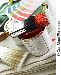 Stack Of Paint Brushes, Paint Tins And Color Wheels