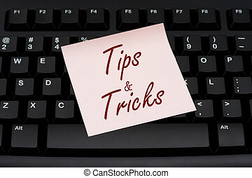 Tips and Tricks - Computer keyboard with a pink sticky note...