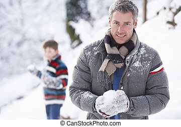 Father And Son Having Snowball Fight In Winter Landscape