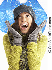 Young Woman Wearing Warm Winter Clothes And Hat Throwing...