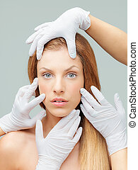 young woman being examinated plastic surgeons' hands -...