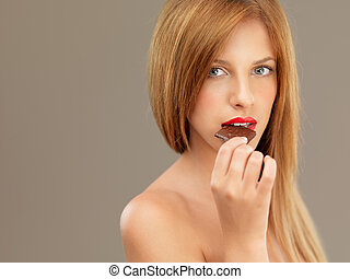 sexy blonde woman red lips tasting chocolate