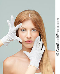 young woman being examinated plastic surgeons' hands
