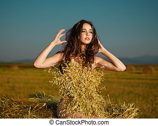 beautiful nude woman posing on hay stack - fashion portrait...