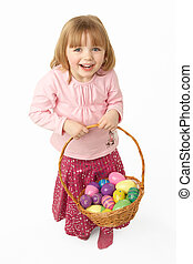 Young Girl Carrying Basket Filled With Easter Eggs