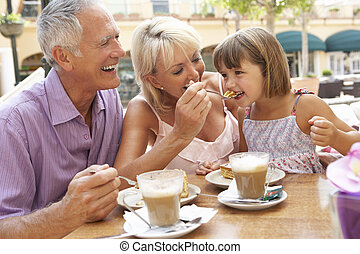 Grandparents With Granddaughter Enjoying Coffee And Cake In...