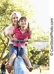 Grandmother And Granddaughter Riding On See Saw In...