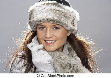 Studio Portrait Of Young Woman Wearing Fur Hat And Wrap