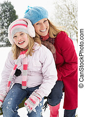 Mother And Daughter Standing Outside In Snowy Landscape
