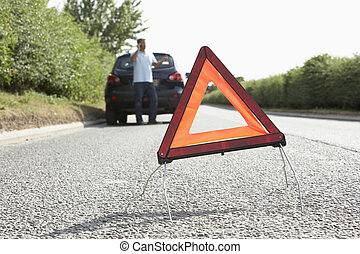 Driver Broken Down On Country Road With Hazard Warning Sign...