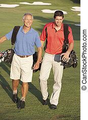 Two Men Walking Along Golf Course Carrying Bags