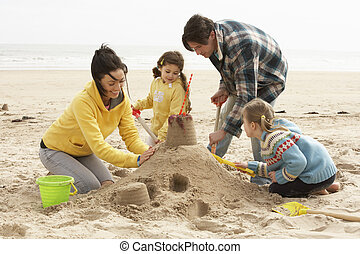 Family Building Sandcastle On Winter Beach