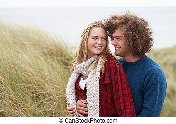 Teenage Couple Walking Through Sand Dunes Wearing Warm Clothing