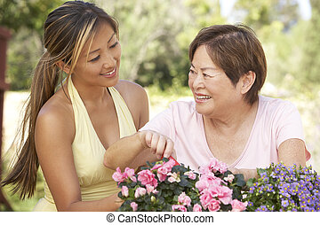 Mother With Adult Daughter Gardening Together