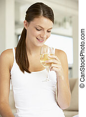 Young Woman Enjoying A Glass Of White Wine