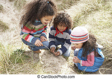 Children Playing In Dunes On Winter Beach