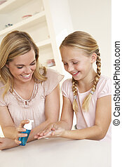 Mother putting sanitizer on young girls hands