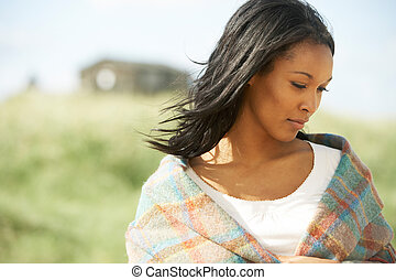 Thoughtful Young Woman Standing On Beach Wrapped In Blanket