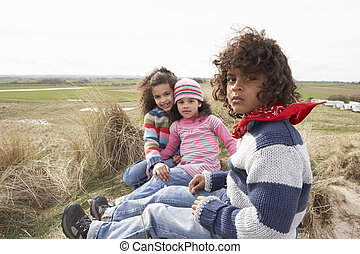 Children Sitting Amongst Dunes On Winter Beach