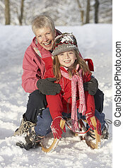 Young Girl With Grandmother Riding On Sledge In Snowy...