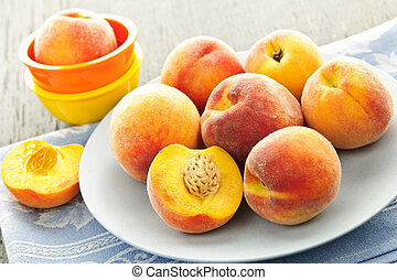 Peaches on plate - Ripe juicy peaches on a plate ready to...