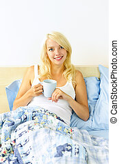 Pretty woman sitting in bed with coffee cup