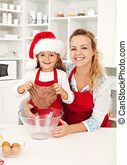 Christmas woman and little girl making gingerbread cookies
