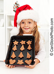 Happy christmas girl baking cookies in the kichen showing...