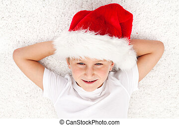 Happy kid at christmas time laying on the floor