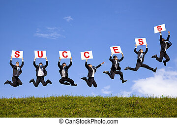 happy businessman holding success text  and jumping on the green field