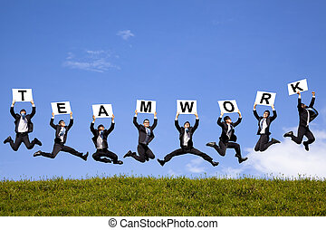 happy businessman holding teamwork text and jumping on the...
