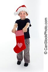 Smiling boy holding christmas stocking in front of him