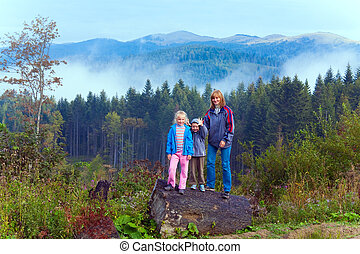 Family on september Carpathian mountain hill and cloudy...