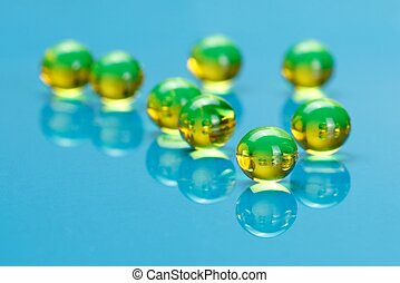 Macro of E vitamines on blue - Macro of shiny, yellow E...