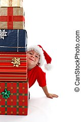 Young boy smiling behind presents