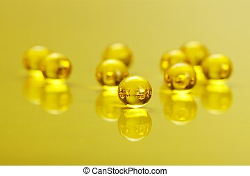 Macro of E vitamine capsules on yellow - Macro of shiny,...