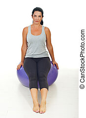 Woman sitting on pilates ball - Woman sitting and resting on...