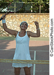 Successful tennis woman cheering and raising hands with...