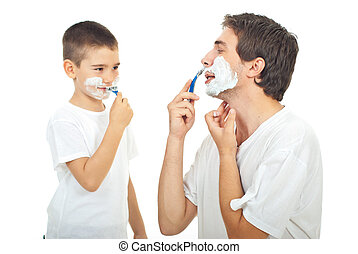 Father and son shaving together - Father teaching his son to...
