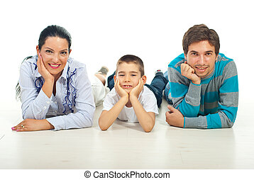 Happy family sitting on floor in a row and smiling